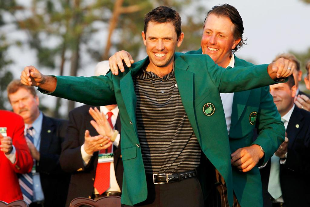 Phil Mickelson helps Charl Schwartzel don the green jacket. Copyright Reuters.